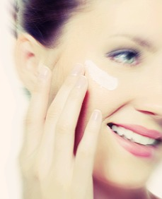 Pretty smiling female applying cosmetic cream on skin of face - isolated